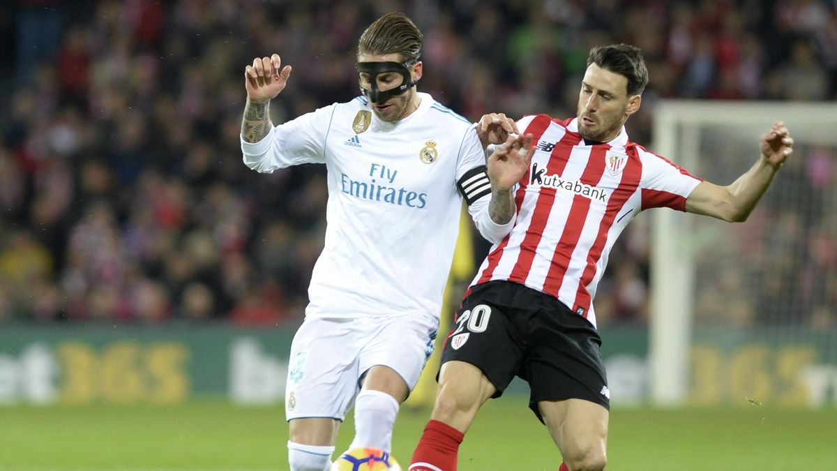 Real Madrid's Spanish defender Sergio Ramos (L) challenges Athletic Bilbao's Spanish forward Aritz Aduriz during the Spanish league football match Athletic Club Bilbao vs Real Madrid CF at the San Mames stadium in Bilbao on December 2, 2017.