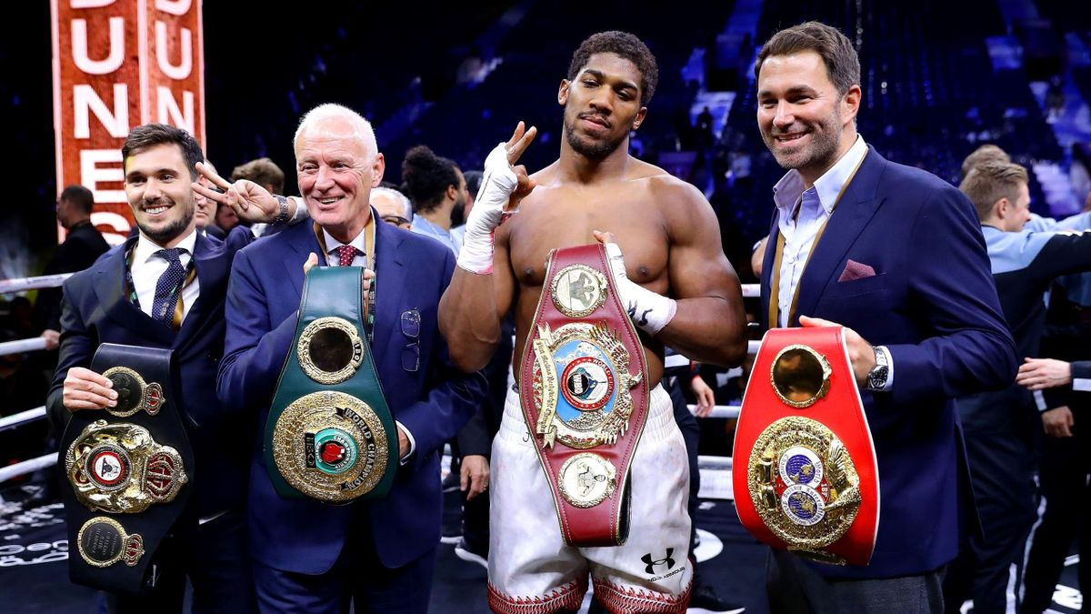 Anthony Joshua poses for a photo with the IBF, WBA, WBO & IBO World Heavyweight Title belts with Eddie Hearn and Barry Hearn