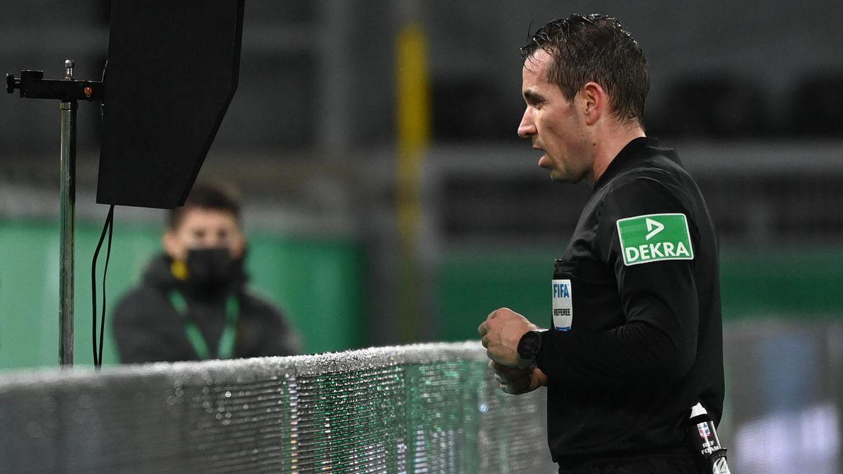 Tobias Stieler schaut in der Nachspielzeit auf den Videobeweis