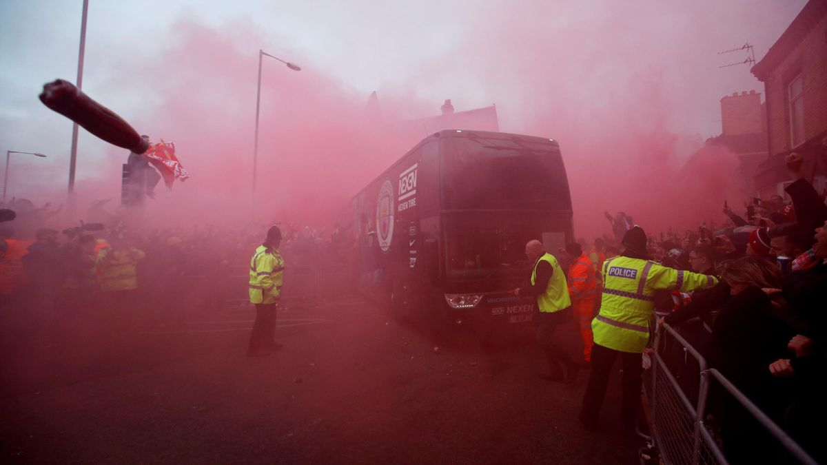 Liverpool fans set off flares and throw missiles at the Manchester City team bus outside the stadium before the match