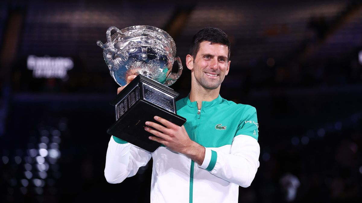 Novak Djokovic of Serbia holds the Norman Brookes Challenge Cup as he celebrates victory in his Men's Singles Final match against Daniil Medvedev of Russia during day 14 of the 2021 Australian Open at Melbourne Park
