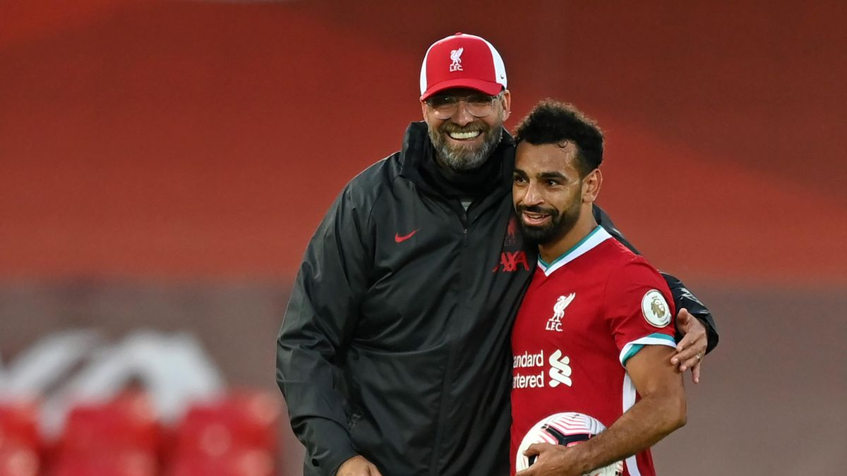 Liverpool's Egyptian midfielder Mohamed Salah (R) takes the match ball as he walks off with Liverpool's German manager Jurgen Klopp (L)