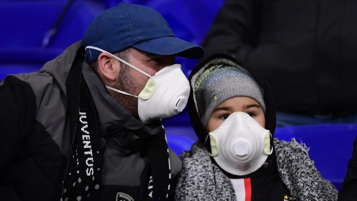 Supporters wearing masks to protect against the Coronavirus during the UEFA Champions League round of 16 first leg match between Lyon and Juventus at Groupama Stadium on February 26, 2020 in Lyon, France