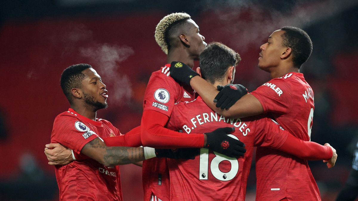 Manchester United's Portuguese midfielder Bruno Fernandes (C) celebrates with teammates after scoring their second goal from the penalty spot during the English Premier League football match between Manchester United and Aston Villa at Old Trafford in Man