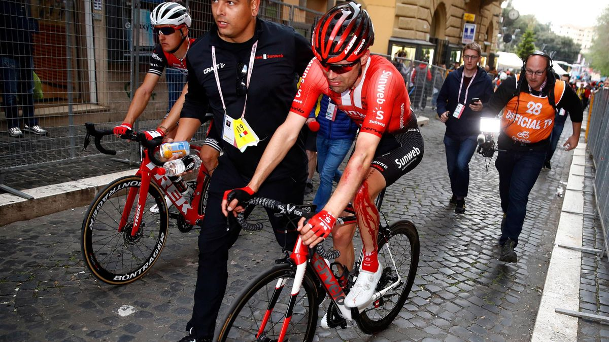 Team Sunweb rider Netherlands' Tom Dumoulin is escorted by a staff member after a crash in the stage four of the 102nd Giro d'Italia - Tour of Italy - cycle race, 235kms from Orbetello to Frascati on May 14, 2019