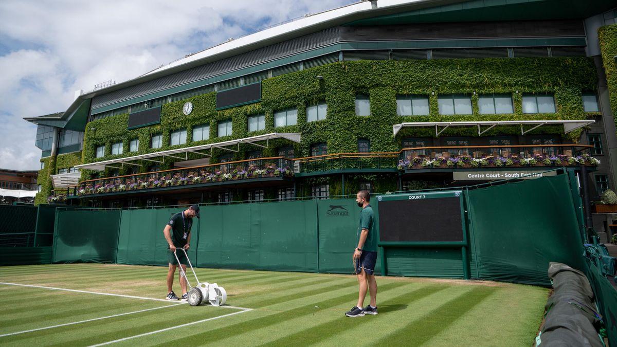 Dos operarios trabajan en las pistas del All England Tennis Club de Wimbledon 2021
