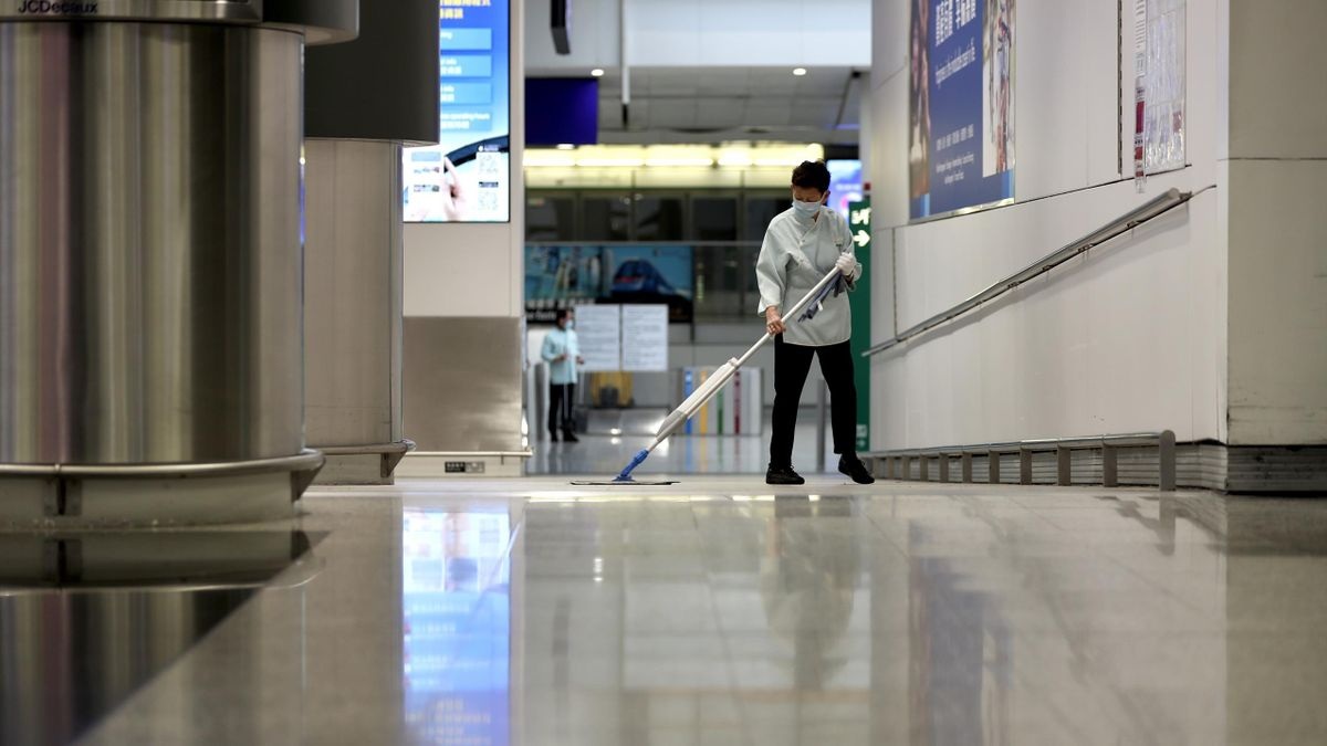 Cleaner wearing mask while cleaning at the Hong Kong Airport. Since the outbreak of the Corona Virus epidemic in Wuhan, China, concerns have risen about how the virus might be spread by air travelers. Flight attendants and pilots are now wearing face mask
