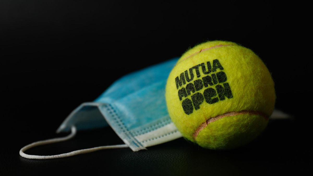 An official ball from the Mutua Madrid Open professional tennis tournament together with a surgical mask