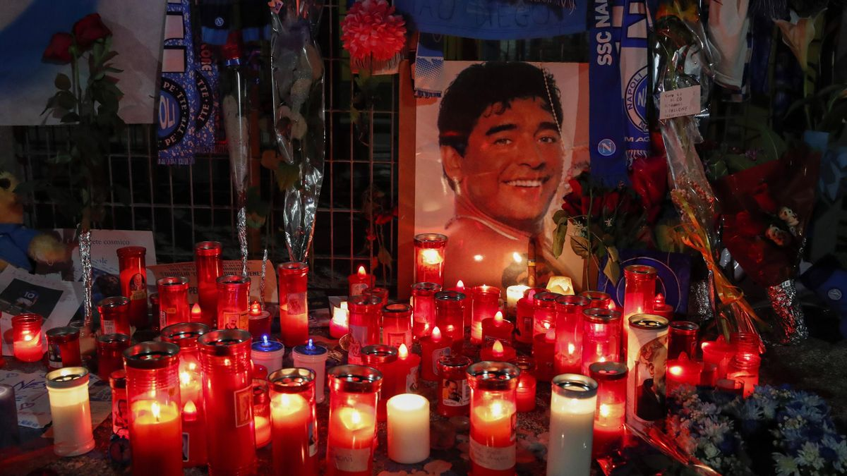 Mourning candles are next to a picture and tributes and memorabilia from supporters to football legend Diego Armando Maradona