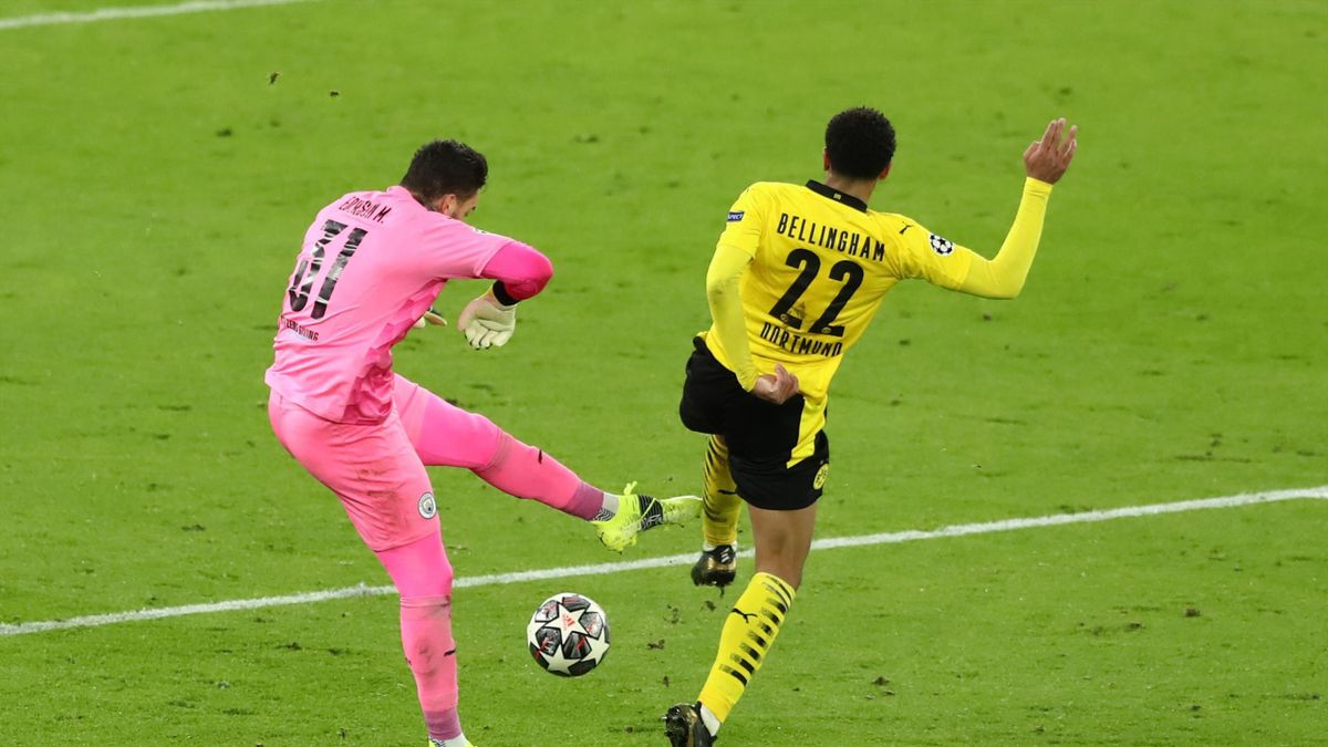 Jude Bellingham of Borussia Dortmund tackles Ederson of Manchester City to win the ball during the UEFA Champions League Quarter Final match between Manchester City and Borussia Dortmund at Etihad Stadium on April 06, 2021 in Manchester, England.