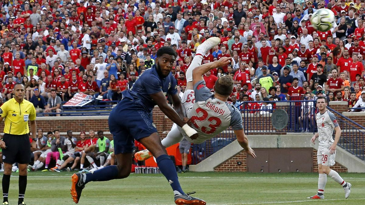 Liverpool FC Sheridan Shaqiri (R) shoots and scores during the second half of the 2018 International Champions Cup football match against Manchester United at Michigan Stadium in Ann Arbor, Michigan on July 28, 2018.