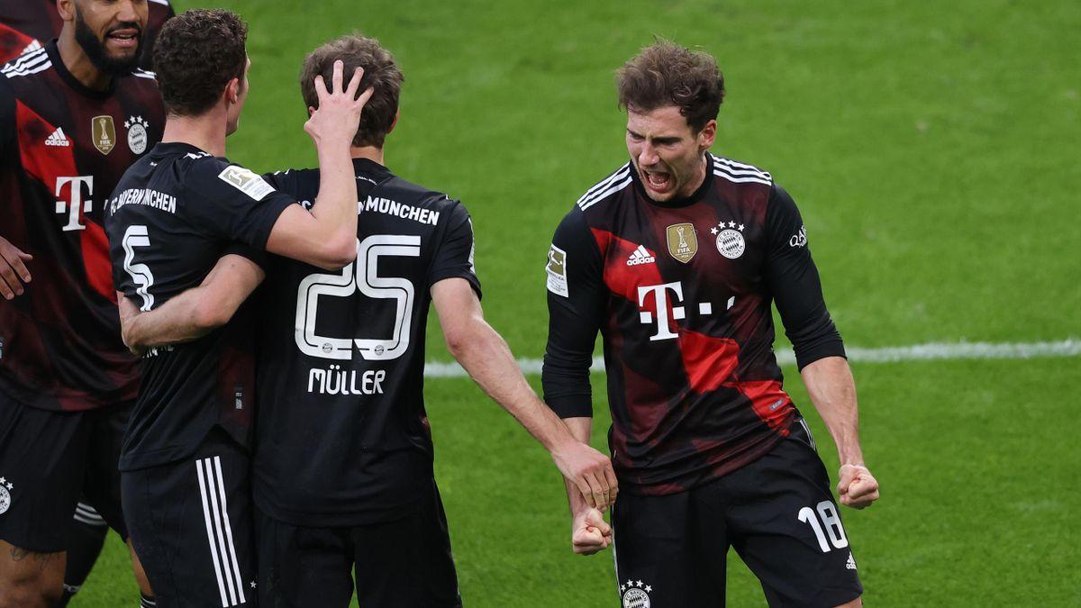 Leon Goretzka of FC Bayern Muenchen celebrates with teammate Benjamin Pavard and Thomas Mueller