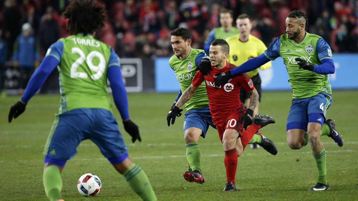 Toronto FC forward Sebastian Giovinco (10) battles with Seattle Sounders midfielder Cristian Roldan (7) and Seattle Sounders defender Tyrone Mears (4) during Seattle's MLS Cup final victory over Toronto FC at BMO Field on December 10, 2016 in Toronto