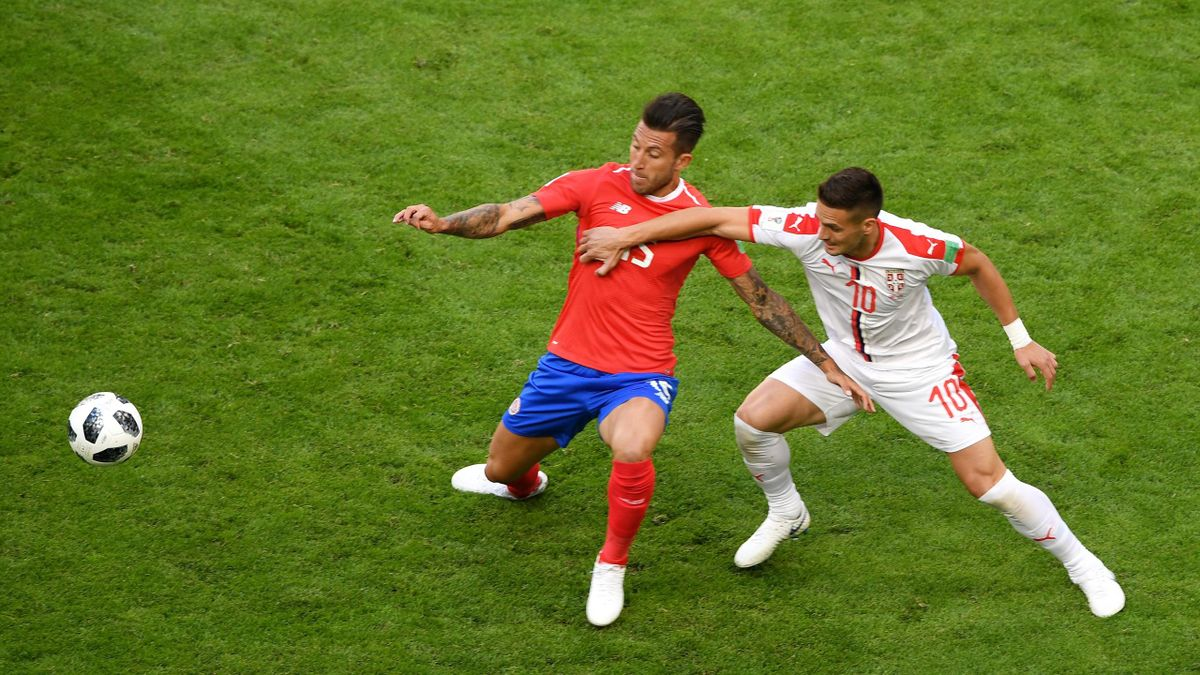 Francisco Calvo of Costa Rica battles for possession with Dusan Tadic of Serbia