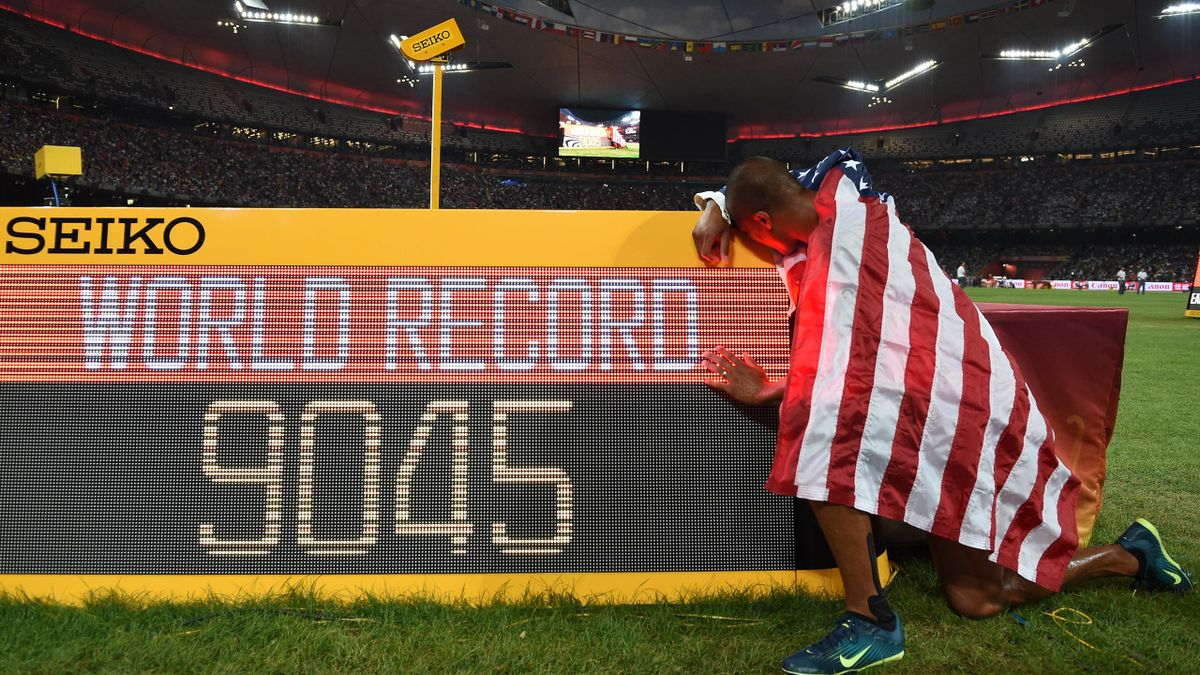 USA's Ashton Eaton poses next to the scoreboard showing Eaton's points total, a new world record, after finishing the 1500 metres