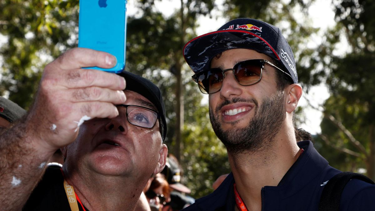 Red Bull Racing driver Daniel Ricciardo of Australia poses for a picture with a fan as he arrives at the track.