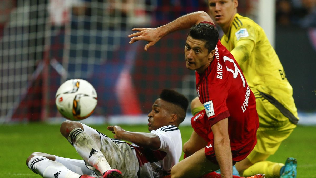 Bayer Leverkusen's Wendell (L) tackles Polish striker Robert Lewandowski of Bayern Munich as Leverkusen goal keeper Bernd Leno looks on during their German first division Bundesliga soccer match in Munich, Germany August 29, 2015