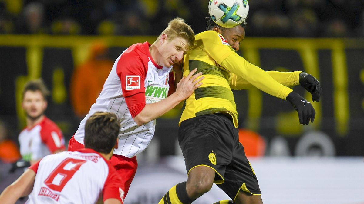 Dortmund's Belgian striker Michy Batshuayi (R) and Augsburg's Austrian defender Martin Hinteregger (C) vie for the ball during the German first division Bundesliga football match Borussia Dortmund vs FC Augsburg, in Dortmund, on February 26, 2018.