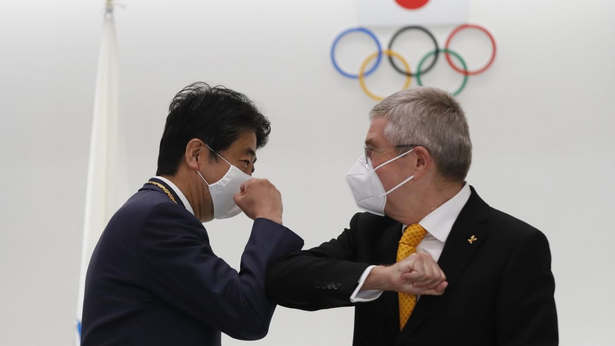 Japan's former Prime Minister Shinzo Abe and Thomas Bach, President of the International Olympic Committee (IOC), elbow bump after a ceremony to present the Olympic Order to Abe at Japan Olympic Museum on November 16, 2020 in Tokyo, Japan