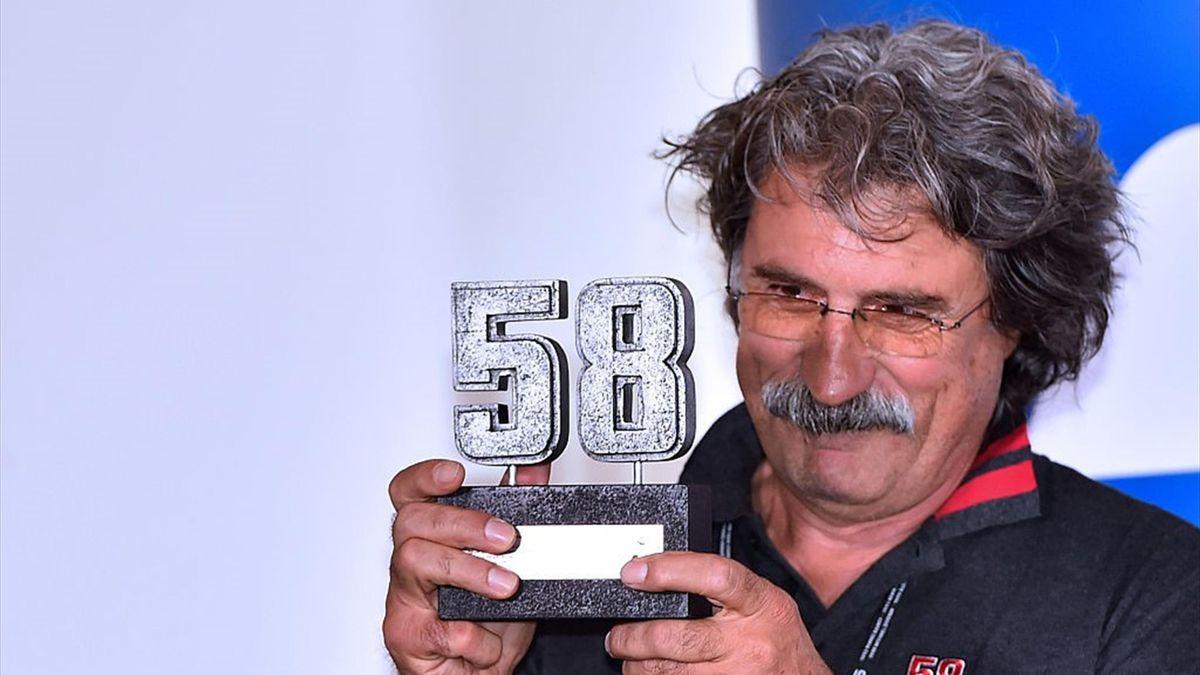 Paolo Simoncelli, papà di Marco, mostra un trofeo dedicato al figlio scomparso il 23 ottobre 2011