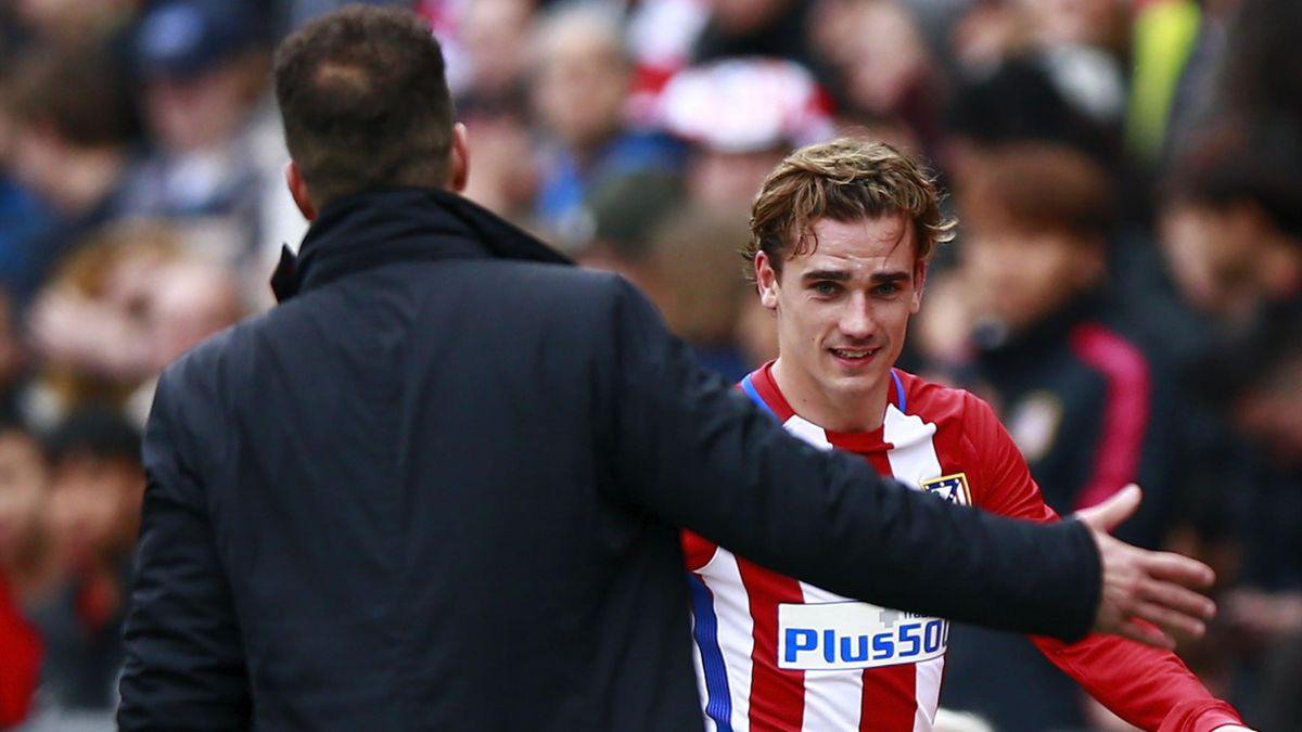 Antoine Griezmann (R) of Atletico de Madrid clashes hands with his coach Diego Pablo Simeone (L)