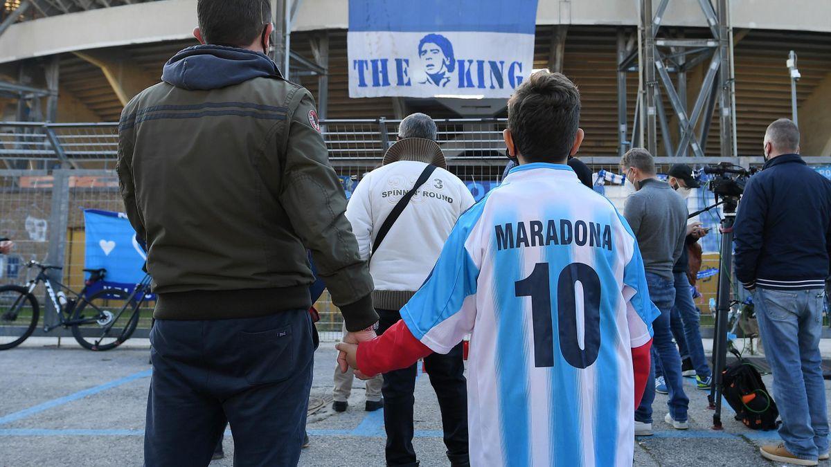 Un père et son fils se recueillant devant le San Paolo pour Maradona