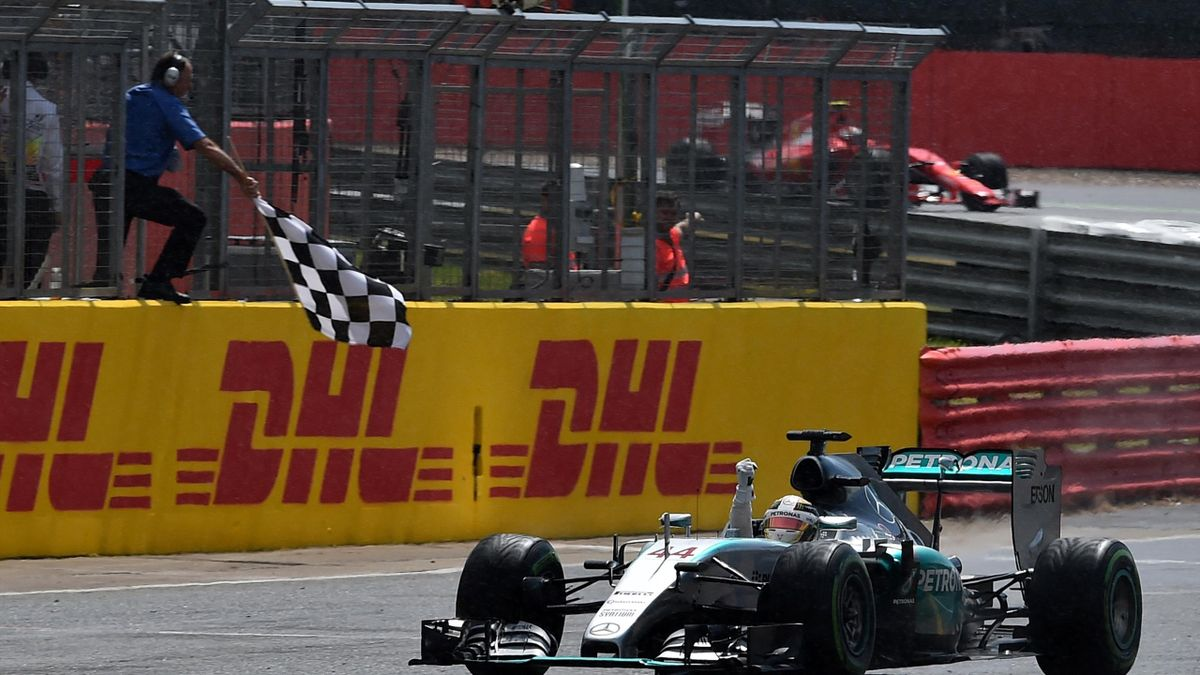 Mercedes AMG Petronas F1 Team's British driver Lewis Hamilton raises his arm as he passes the chequered flag to win the British Formula One Grand Prix at the Silverstone circuit in Silverstone on July 5, 2015.