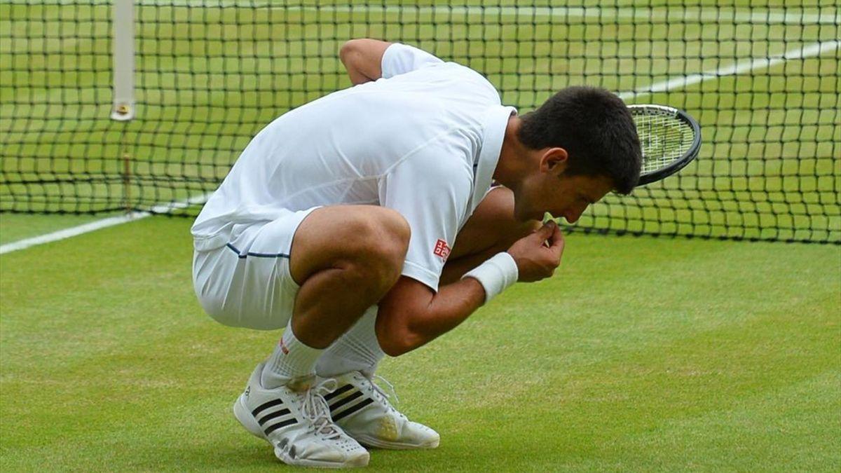 Novak Djokovic celebrates his winning agaisnt Federer eating a blade of grass during their men's singles final match on Centre Court