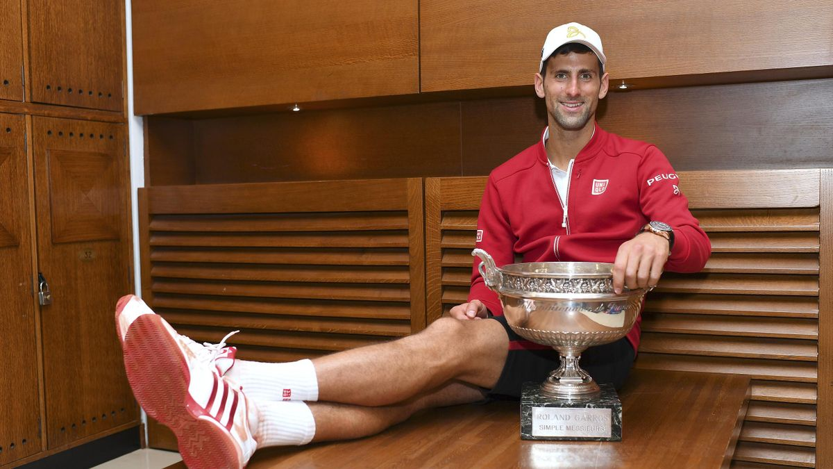 Serbia's Novak Djokovic posing with his trophy in the locker room after winning the men's final match against Britain's Andy Murray at the Roland Garros 2016 French Tennis Open in Paris on June 5, 2016