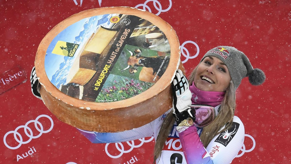 Lindsey Vonn holds a cheese as she celebrates on the podium after winning the women's Super-G race at the FIS Alpine Skiing World Cup in Val-d'Isere, French Alps
