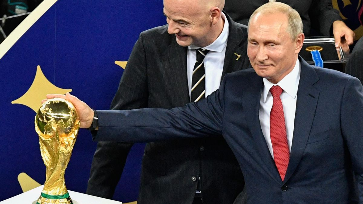 Russian President Vladimir Putin (R) caresses the trophy next to FIFA president Gianni Infantino (C) during the trophy ceremony at the end of the Russia 2018 World Cup final football match between France and Croatia at the Luzhniki Stadium.