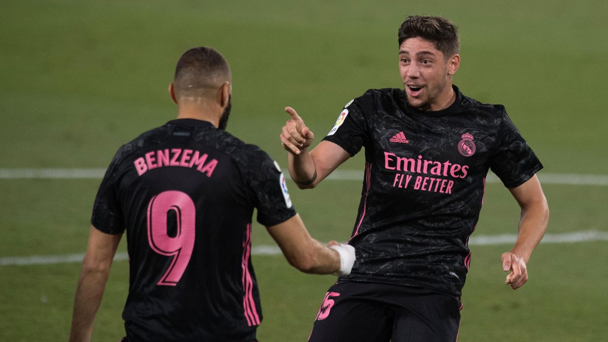 Real Madrid's Uruguayan midfielder Valverde celebrates with French forward Karim Benzema after scoring during the Spanish league football match Real Betis against Real Madrid CF at the Benito Villamarin stadium in Seville on September 26, 2020