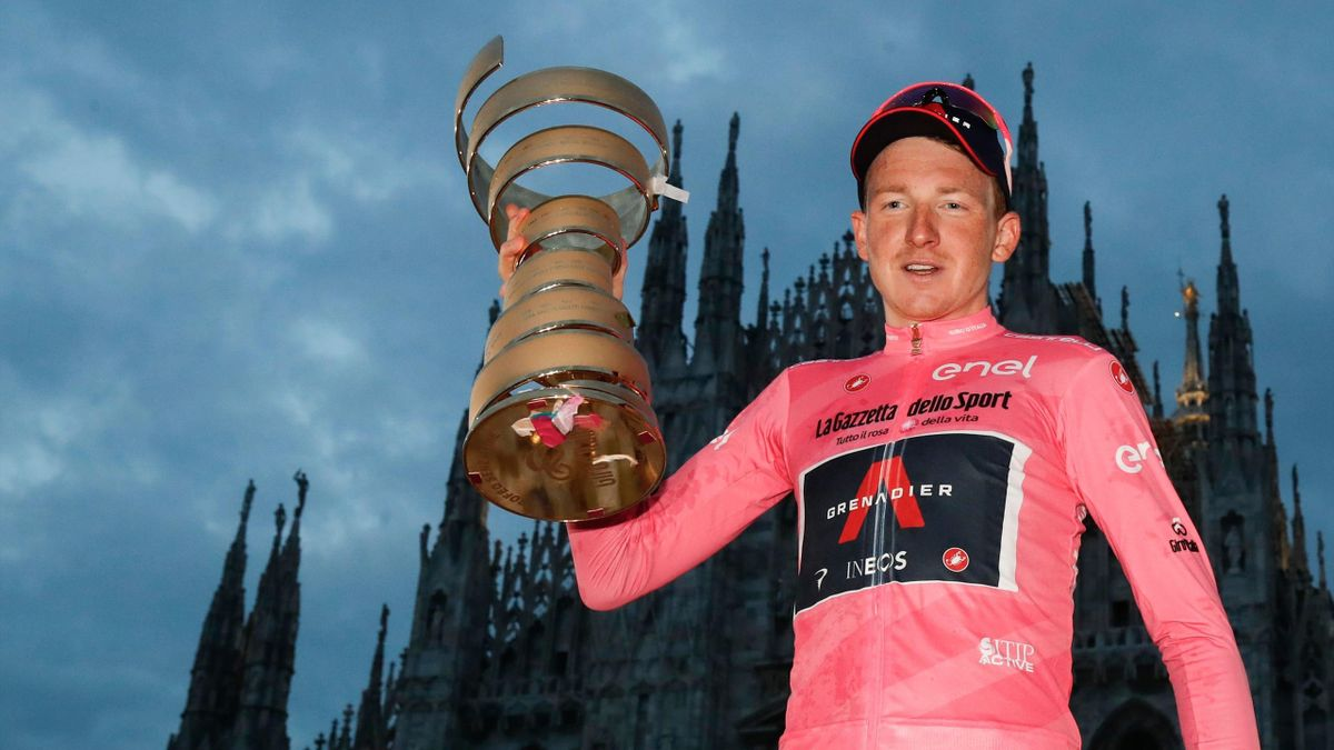 "Overall race winner Team Ineos rider Great Britain's Tao Geoghegan Hart wearing the leader's pink jersey holds the ""Never ending trophy"" (Trofeo Senza Fine) as he celebrates on podium in front of the Duomo cathedral, after the the 21st and final stage of"