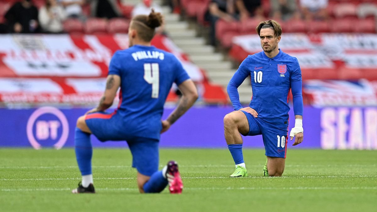 Kalvin Phillips (L) and Jack Grealish take a knee