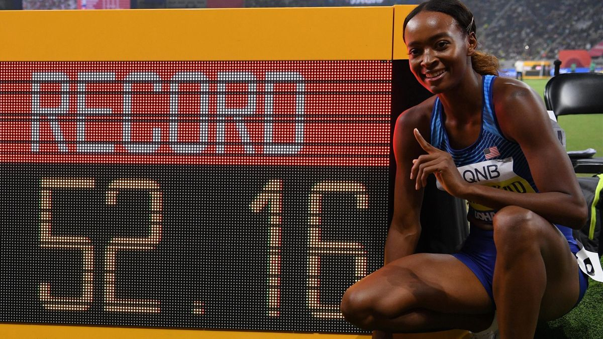 USA's Dalilah Muhammad celebrates after winning and poses next to the screen reading the new world record in the Women's 400m Hurdles final at the 2019 IAAF Athletics World Championships at the Khalifa International stadium in Doha on October 4, 2019