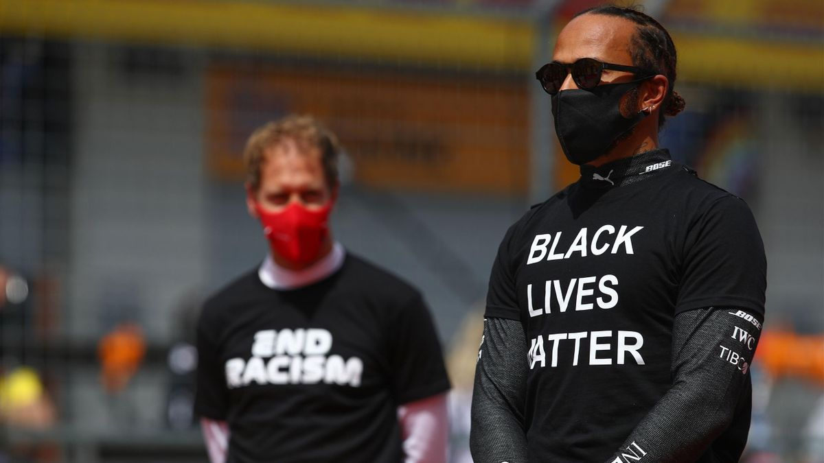 Sebastian Vettel (L) and Lewis Hamilton take part in an anti-racism protest