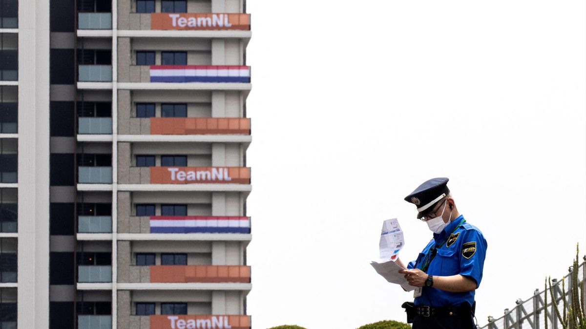 Een Japanse agent neemt papierwerk door met op de achtergrond het onderkomen van de Nederlandse atleten