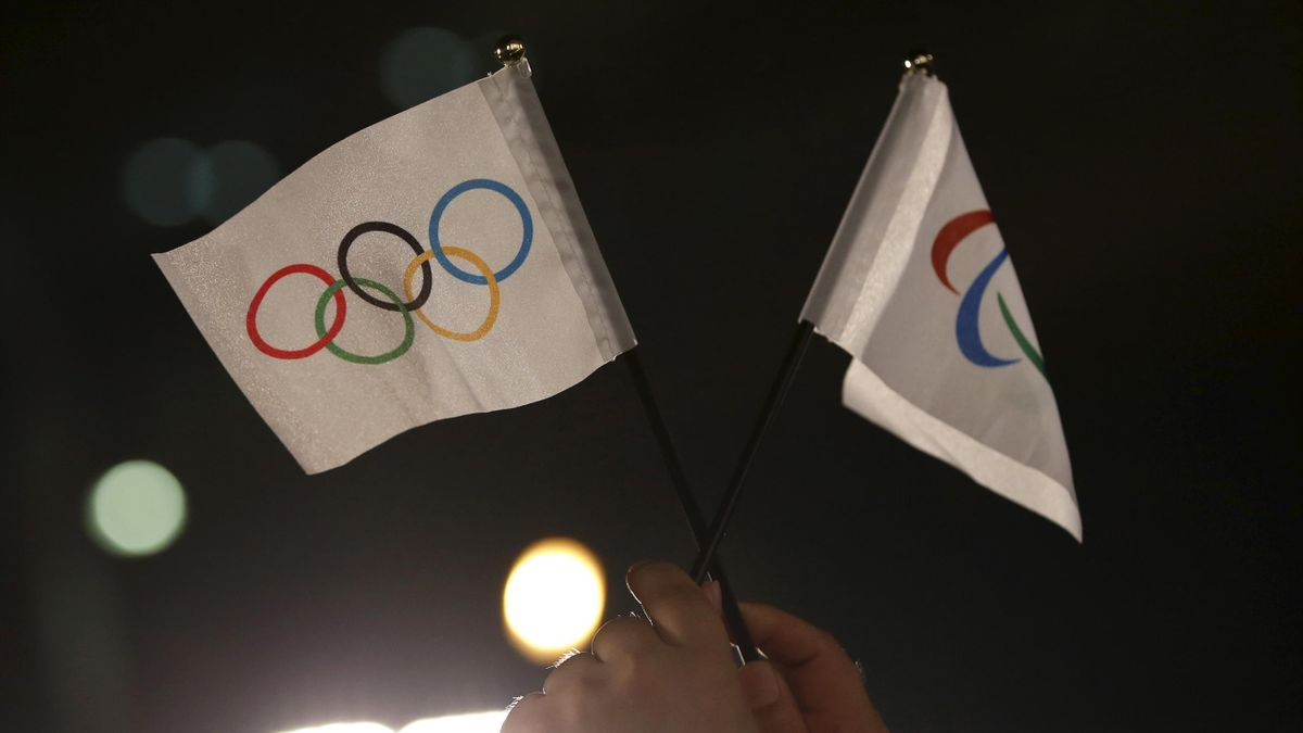 A spectator waves Olympic and Paralympic flags