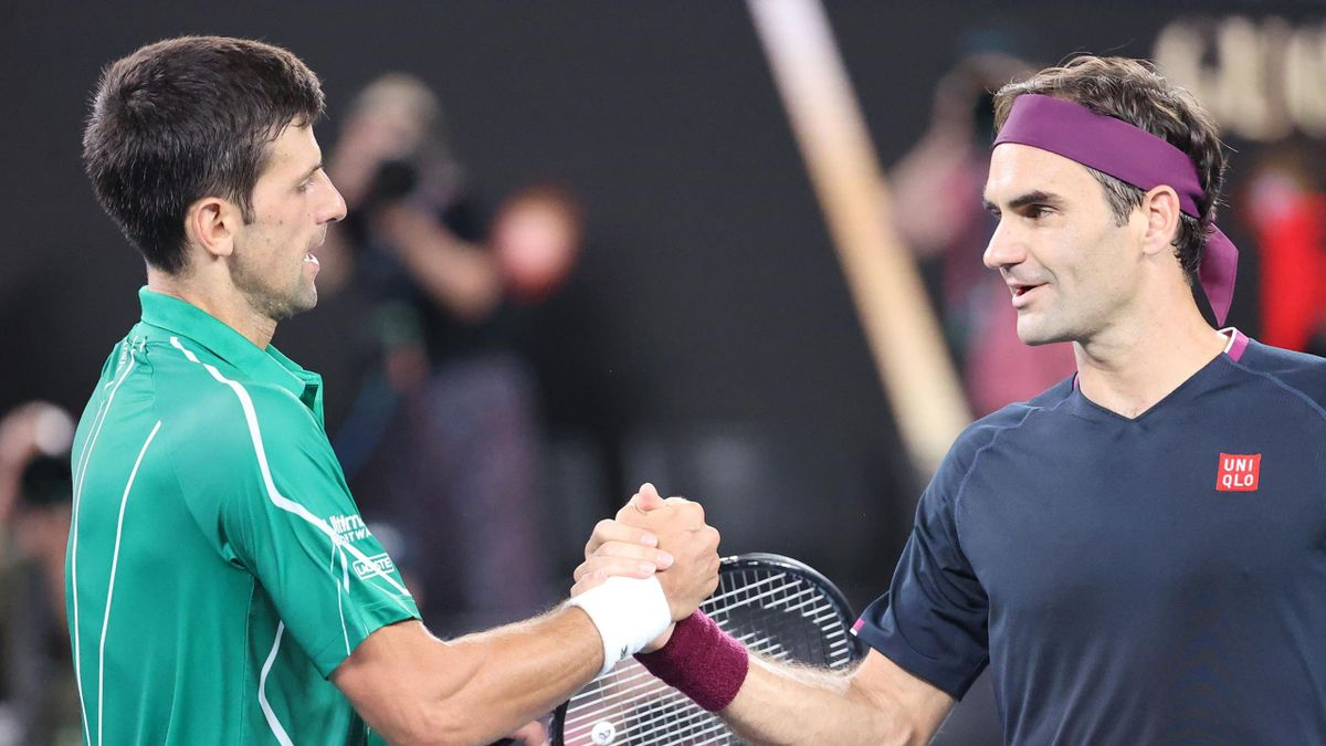 Serbia's Novak Djokovic (L) shakes hands with Switzerland's Roger Federer after his victory during their men's singles semi-final match on day eleven of the Australian Open tennis tournament in Melbourne on January 30, 2020