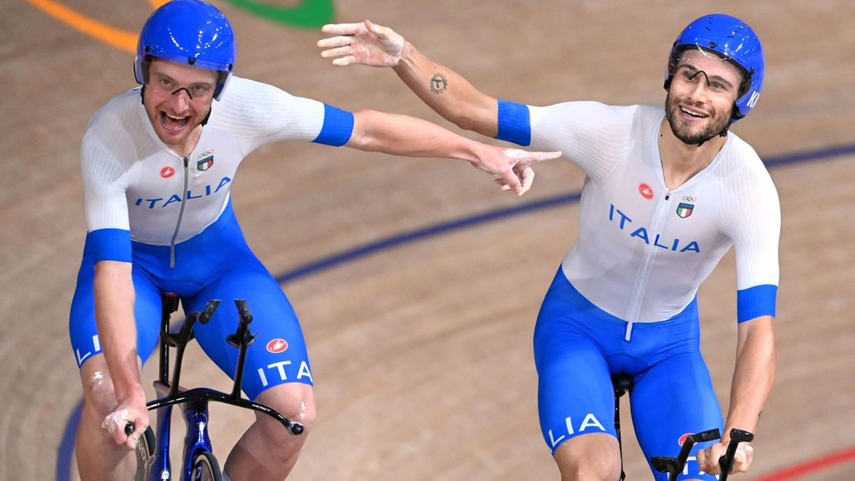 Italy's Simone Consonni (L) and Italy's Filippo Ganna celebrate after winning gold and setting a new World Record in the men's track cycling team pursuit finals during the Tokyo 2020 Olympic Games at Izu Velodrome in Izu, Japan, on August 4, 2021