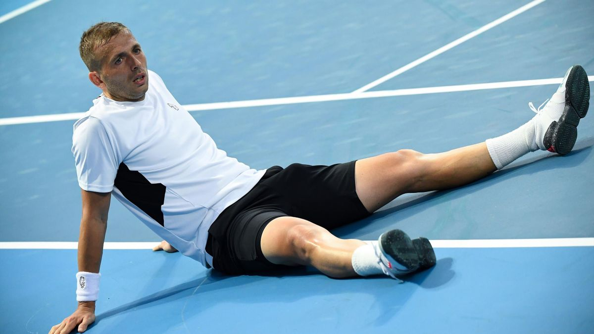 Daniel Evans sits on the court after falling while playing against Britain's Cameron Norrie during their men's singles match on day two of the Australian Open tennis tournament in Melbourne on February 9