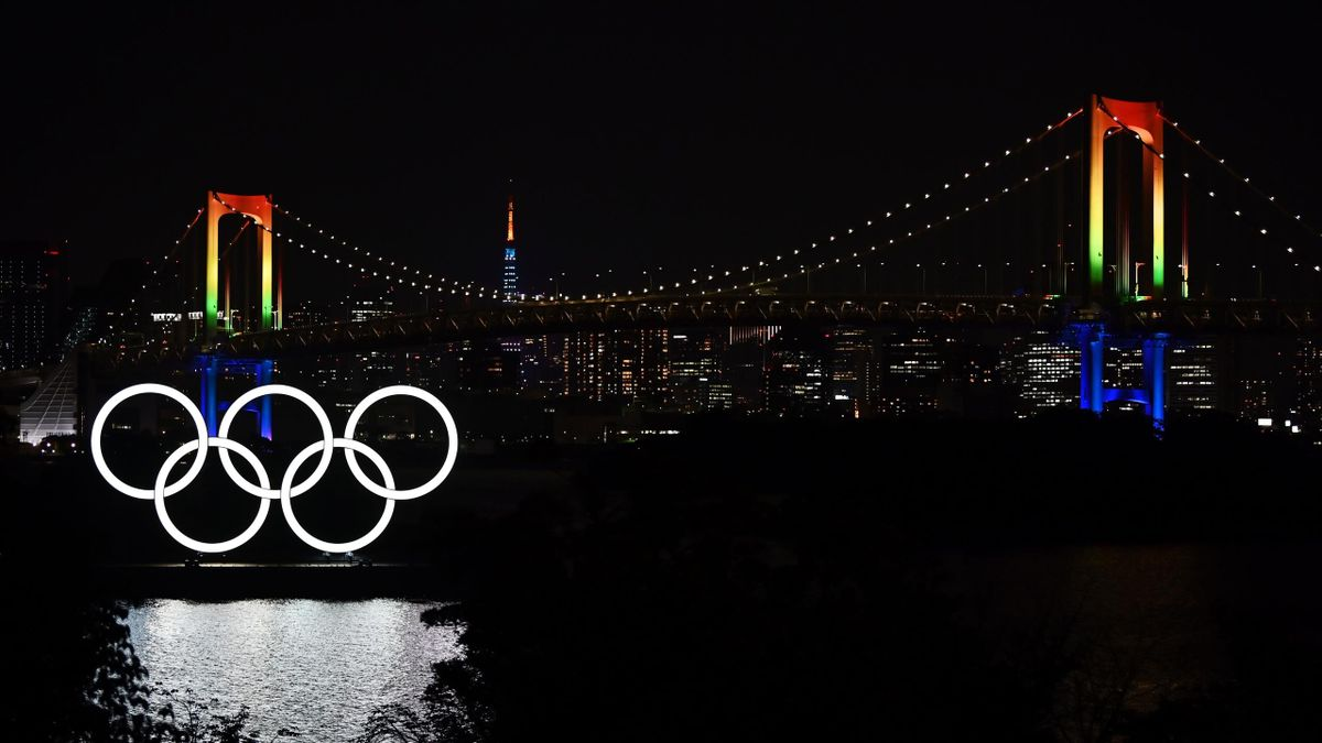The Olympic rings, the Rainbow bridge and the Tokyo Tower are pictured at night from Tokyo's Odaiba area on May 29, 2020