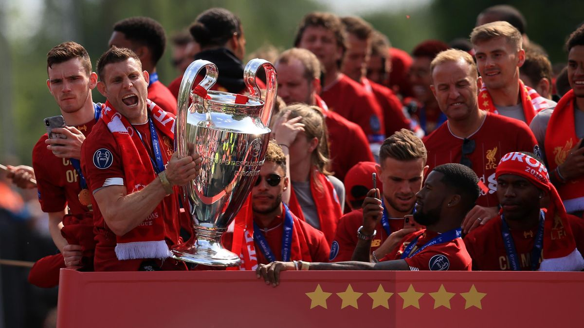 Liverpool FC celebration parade after their Champions League final win over Tottenham Hotspur in Madrid on 1st June; James Milner of Liverpool lifts the trophy at the front of the open top bus