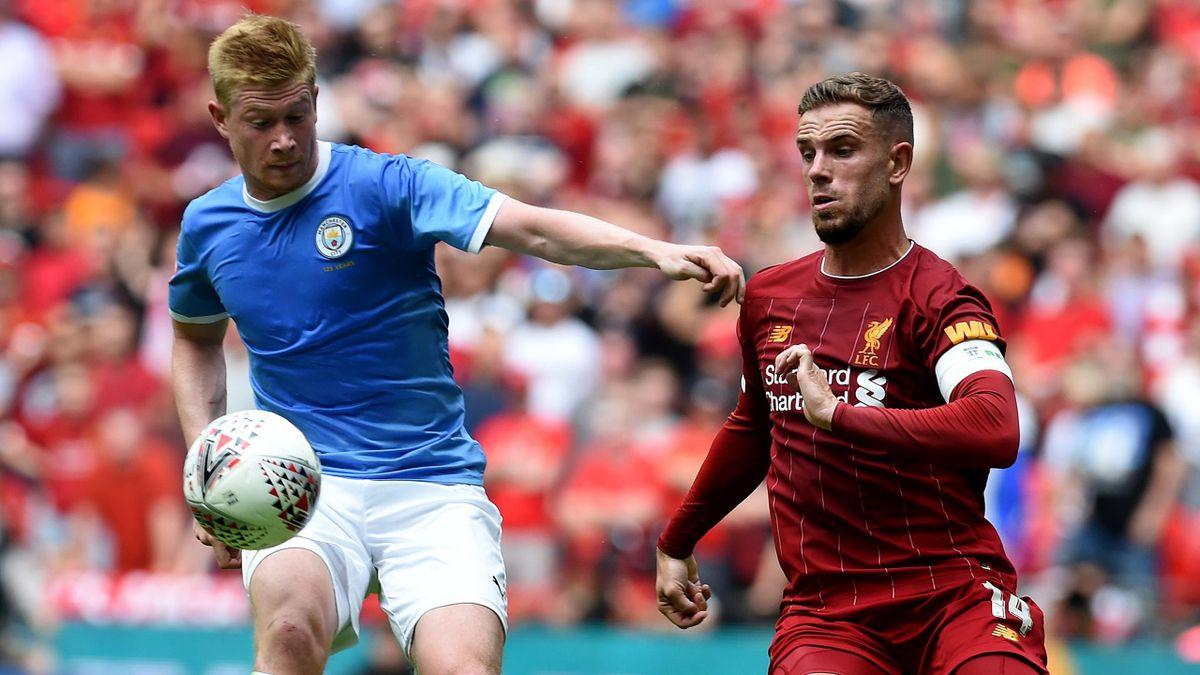 Manchester City's Kevin De Bruyne holds off Liverpool captain Jordan Henderson.