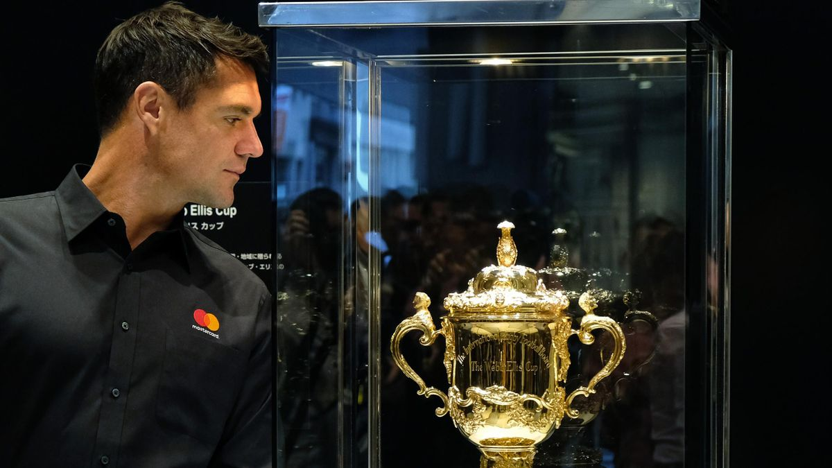 Former All Blacks' player Dan Carter looks at the Webb Ellis Cup, the trophy awarded to the winner of the Rugby World Cup, displayed at a commercial event for the Rugby World Cup 2019 in Tokyo on November 8, 2018.