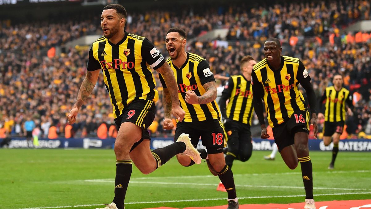 Watford's English striker Troy Deeney (L) celebrates with Watford's English striker Andre Gray (2nd L) and Watford's French midfielder Abdoulaye Doucoure after scoring their late second goal from the penalty spot during the English FA Cup semi-final footb