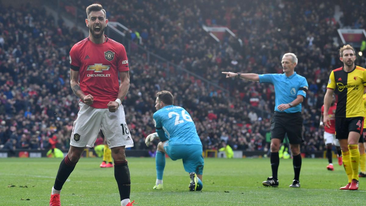 Manchester United's Portuguese midfielder Bruno Fernandes (L) reacts as referee Martin Atkinson (2R) points to the spot to give Manchester United a penalty after Watford's English goalkeeper Ben Foster (C) fouled Fernandes during the English Premier Leagu