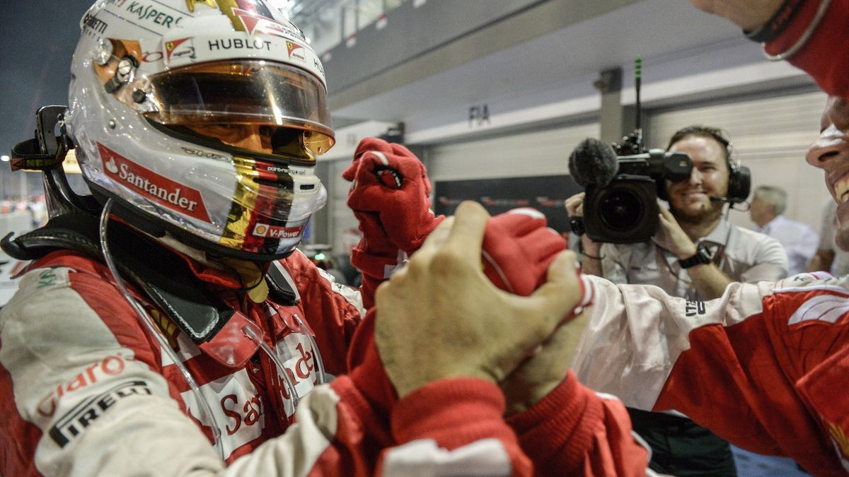 Ferrari's German driver Sebastian Vettel (L) celebrates his victory after winning the Formula One Singapore Grand Prix in Singapore on September 20, 2015.