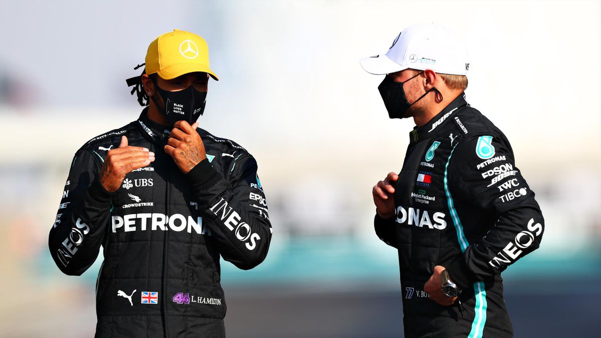 Lewis Hamilton of Great Britain and Mercedes GP talks with teammate Valtteri Bottas of Finland and Mercedes GP on the grid prior to the F1 Grand Prix of Abu Dhabi at Yas Marina Circuit on December 13, 2020 in Abu Dhabi, United Arab Emirates.