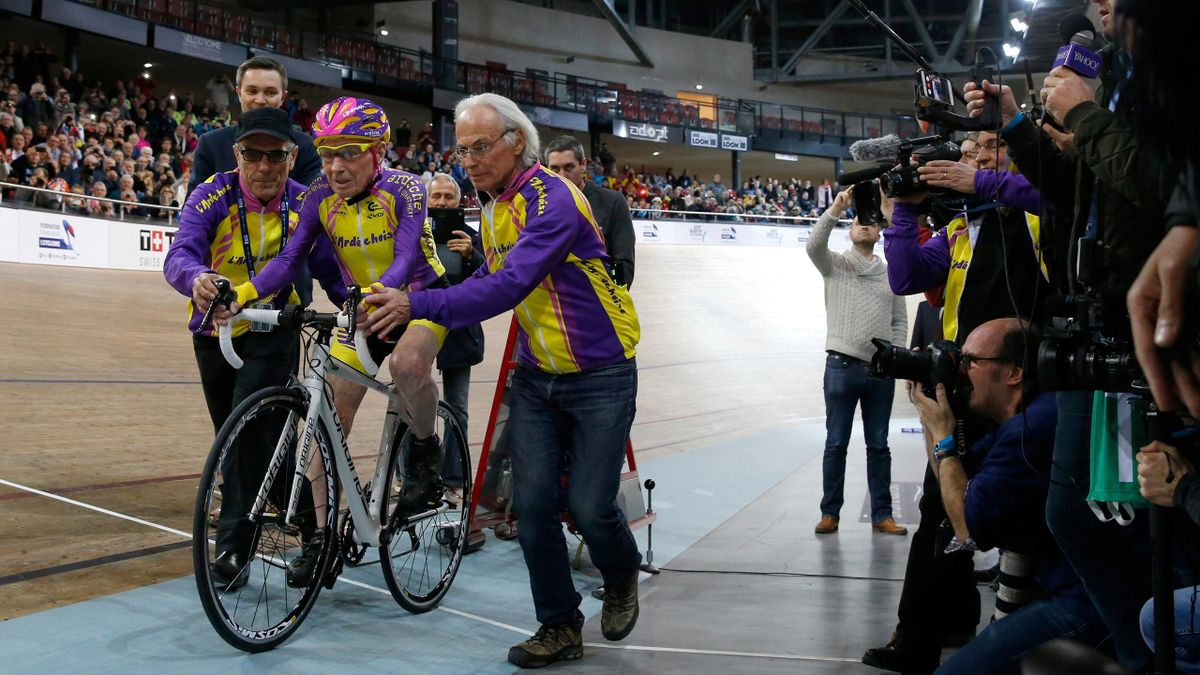 French cyclist Robert Marchand (C) rides his bike as he attempts to break his own world cycling record at the age of 105, taking part in a one-hour cycling event in the Masters